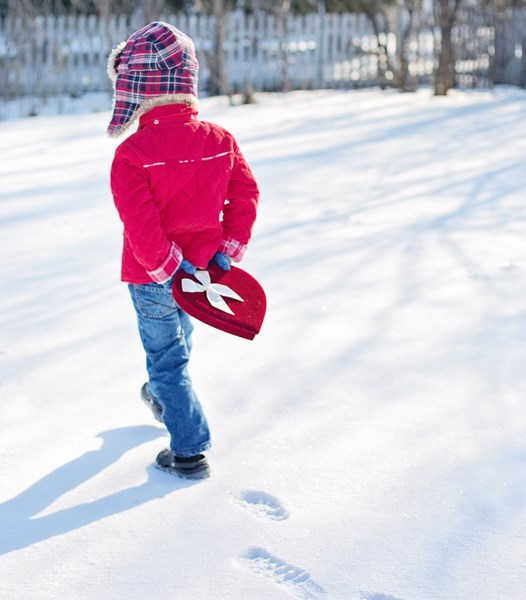 child_in_the_snow_holding_a_heart_box
